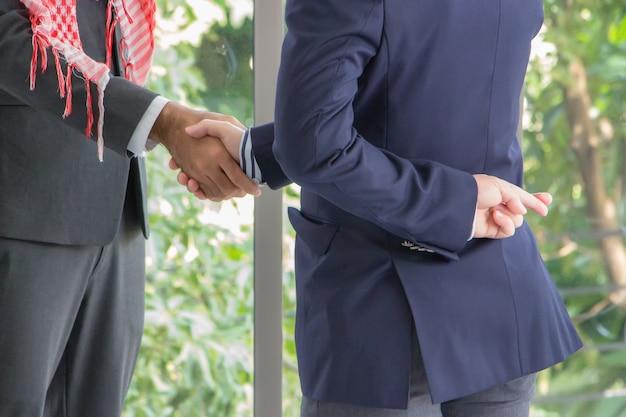 不誠実なビジネスマンと握手するアラブのビジネスマン