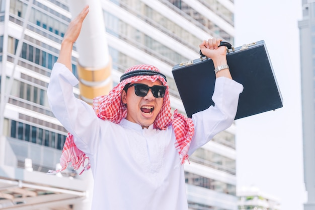 Arab businessman standing by raising both hands up in city