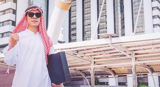 Арабский бизнесмен стоял, подняв обе руки в городе