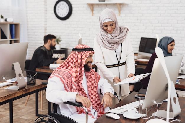 Arab businessman in wheelchair checks report.