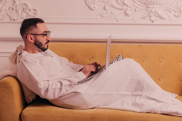 自宅でラップトップコンピューターに取り組んでいるアラブの実業家。高品質の写真