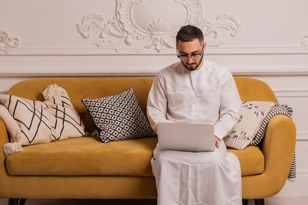 自宅でラップトップコンピューターに取り組んでいるアラブの実業家