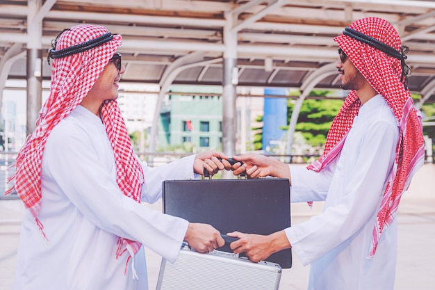아랍 사업가 사람들이 가방을 바꾸고 있습니다.
