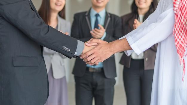 アラブのビジネスマンの握手が実業家の降下と提携