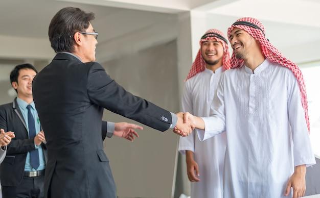 アラブのビジネスマンの握手がビジネスマンの降下と提携