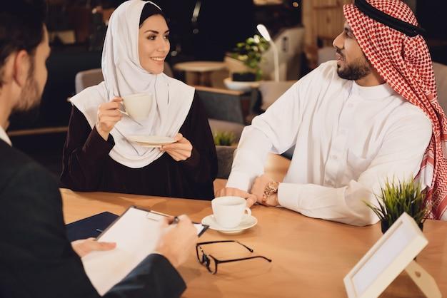アラブのカップルはセラピストのレセプションでコーヒーを飲みます。