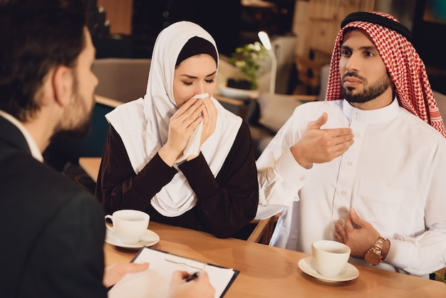 Arab couple drinks coffee at therapist reception.