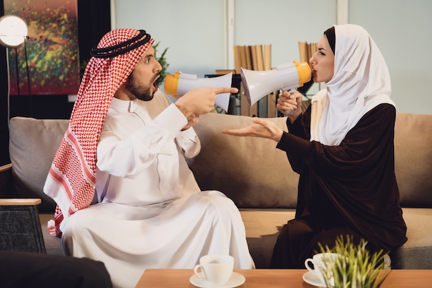 Arab couple screaming at each other in megaphone