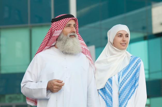 Arab couple smiling and standing on street background
