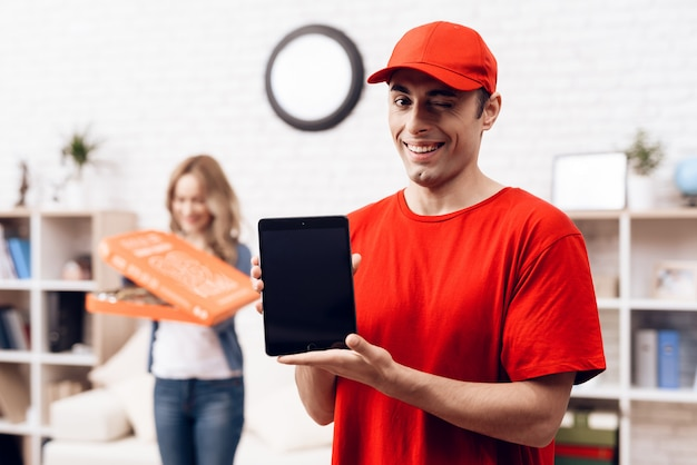 Arab deliveryman with tablet and girl with pizza.