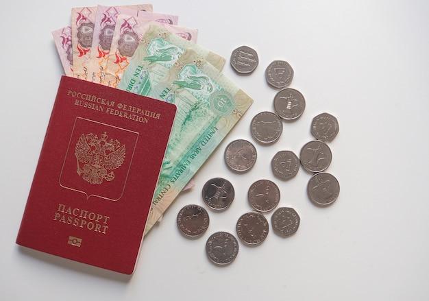 Арабские дирхамы и российский паспорт на белом фоне.