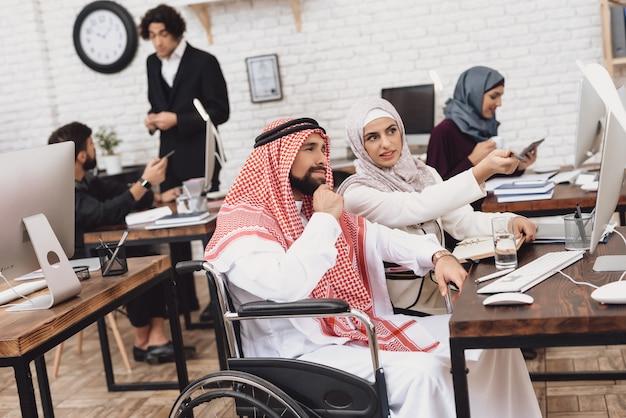 アラブ障害の男性と女性がオフィスで話し合います。