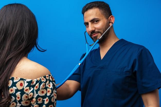 Арабский врач в синей форме стоит со стетоскопом и слушает сердцебиение женщины ...