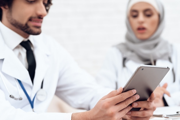 Arab doctor is showing something on a tablet to a colleague.