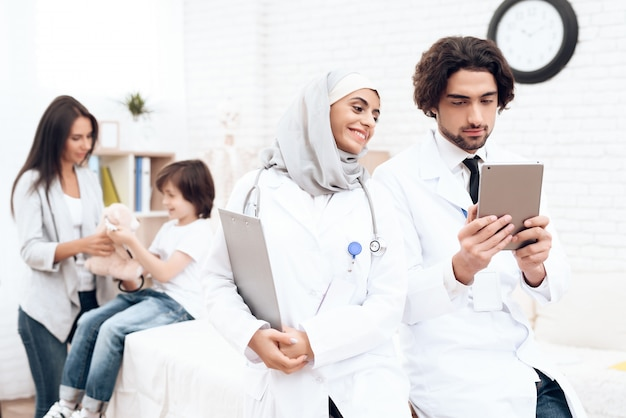 Arab doctors are looking at something on the tablet.