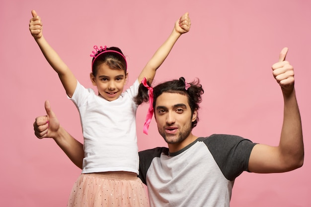 Arab family. dad and daughter. pink background.