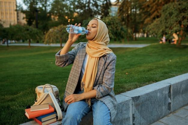 히잡에서 아랍 여성 학생 여름 공원에서 물을 마신다. 잔디밭에 쉬고 책과 무슬림 여성입니다.