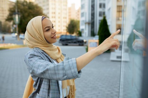 시내에서지도에보고하는 hijab에서 아랍 여성 학생. 비즈니스 센터 입구에 무슬림 여성.