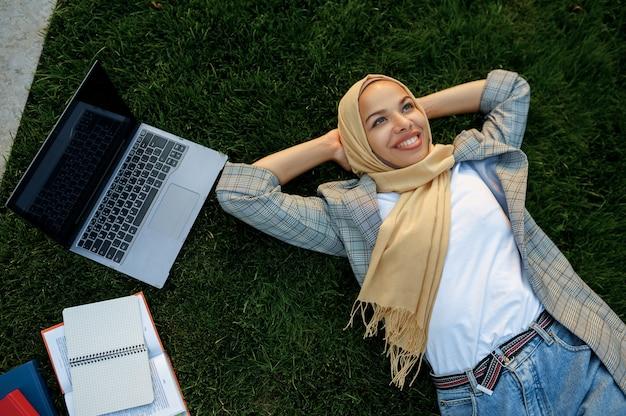 여름 공원, 평면도에서 잔디에 누워 hijab에서 아랍 여성 학생. 잔디밭에 쉬고 책과 무슬림 여성입니다.