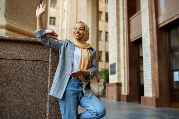 ヒジャーブのアラブの女子学生が大学の入り口で自分撮りをします。本を持ったイスラム教徒の女性が大学の前でポーズをとる。