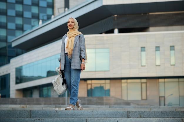 ヒジャーブのアラブの女子学生がダウンタウンの建物でポーズをとる。ビジネスセンターの入り口にいるイスラム教徒の女性。