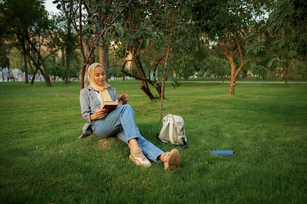 히잡 여름 공원에서 교과서를 읽고 아랍 여성 학생. 잔디밭에 쉬고 책과 무슬림 여성입니다.