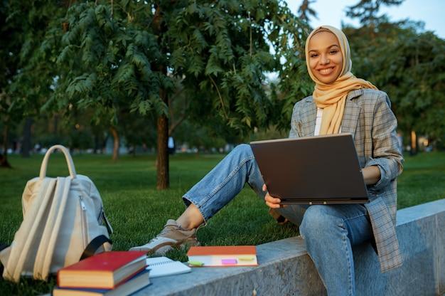 夏の公園でラップトップを使用してヒジャーブのアラブの女子学生。芝生の上で休んでいる本を持つイスラム教徒の女性。