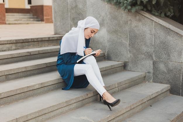 시내 계단에 앉아 아랍 여학생