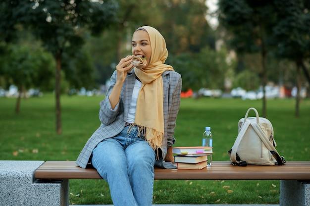 夏の公園のベンチに座っているアラブの女子学生。散歩道で休んでいるイスラム教徒の女性。