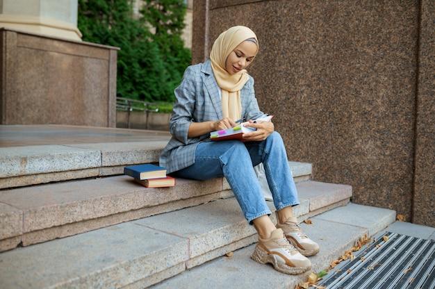 大学の階段に座っているアラブの女子学生。イスラム教徒の女性がビジネスセンターの入り口で化粧をします。