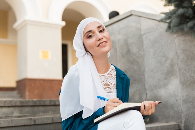 Arab female student sitting on stairs in downtown