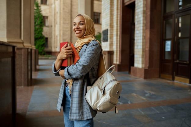 大学の入り口で本を持っているアラブの女子学生。ヒジャーブのイスラム教徒の女性は、屋外で教科書を保持しています。