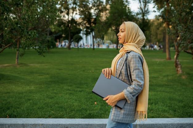 여름 공원에서 산책하는 노트북과 아랍 여성 학생. 도보 경로에 쉬고 이슬람 여성입니다.