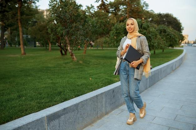 夏の公園を歩いているラップトップを持つアラブの女子学生。散歩道で休んでいるイスラム教徒の女性。