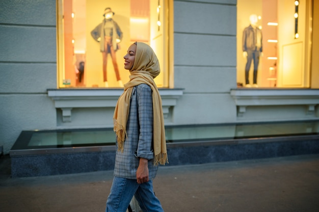 Arab girl in hijab looking on showcase of fashion store in downtown. muslim woman walking on street