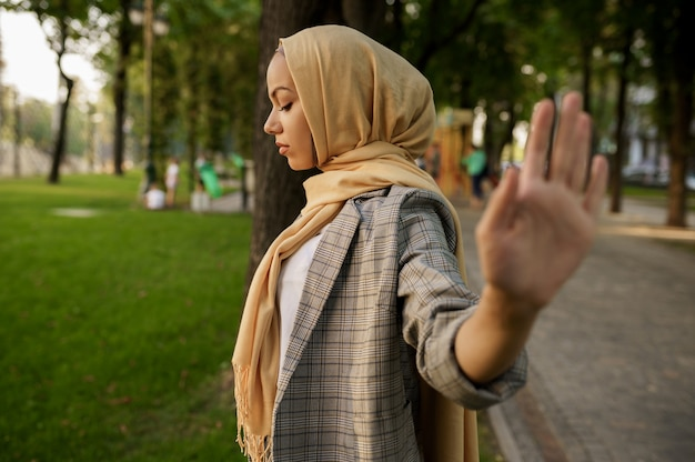 Arab girl in hijab shows her palm in summer park. muslim woman with books resting on the lawn in university campus.