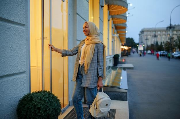ダウンタウンのファッション店の入り口にあるヒジャーブのアラブの女の子。通りを歩いているイスラム教徒の女性。