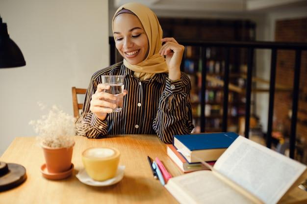 Арабская девушка в хиджабе держит стакан воды, интерьер университетского кафе на фоне. мусульманская женщина с книгами, сидя в библиотеке.