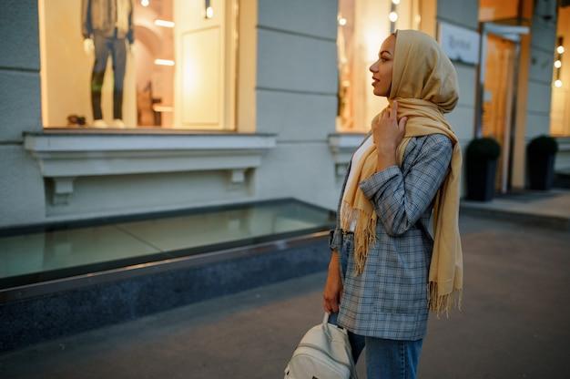 ダウンタウンのファッション店のショーケースを見ているヒジャーブのアラブの女の子。通りを歩いているイスラム教徒の女性。 f