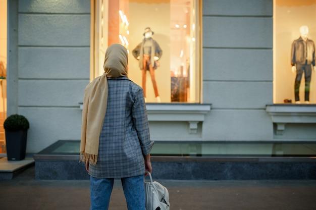 ダウンタウンのファッション店のショーケースを見ているヒジャーブのアラブの女の子。通りを歩いているイスラム教徒の女性