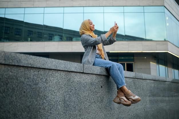 ヒジャーブのアラブの女の子がダウンタウンの建物で自分撮りをします。ビジネスセンターの入り口にいるイスラム教徒の女性。