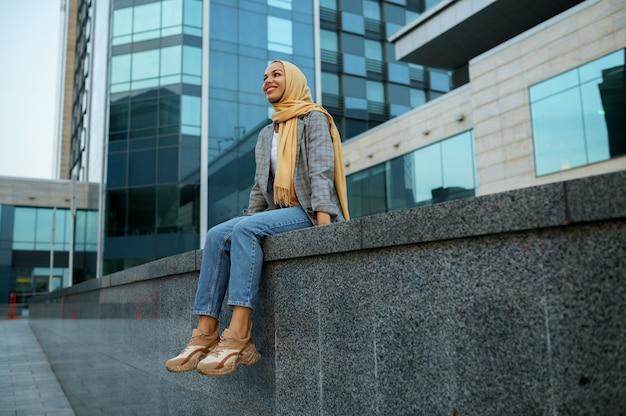 ヒジャーブのアラブの女の子がダウンタウンの建物でポーズをとる。ビジネスセンターの入り口にいるイスラム教徒の女性。
