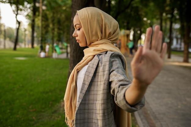 히잡 아랍 소녀는 여름 공원에서 그녀의 손바닥을 보여줍니다. 대학 캠퍼스의 잔디밭에 쉬고 책과 무슬림 여성.