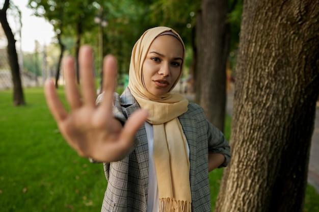 ヒジャーブのアラブの女の子は、夏の公園で彼女の手のひらを示しています。大学のキャンパスの芝生で休んでいる本を持つイスラム教徒の女性。