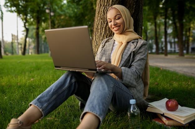 夏の公園でラップトップを使用してヒジャーブのアラブの女の子。大学のキャンパスの芝生で休んでいる本を持つイスラム教徒の女性。