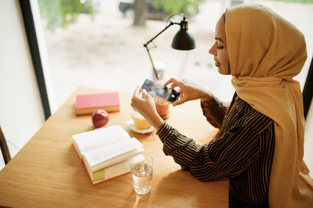 Arab girl makes photo of cup with coffee in university cafe, top view. muslim woman with books sitting in library.