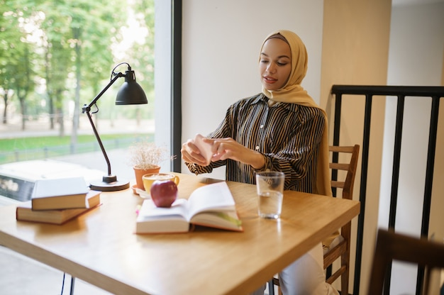 Arab girl makes photo of cup with coffee in university cafe, top view. muslim woman with books sitting in library
