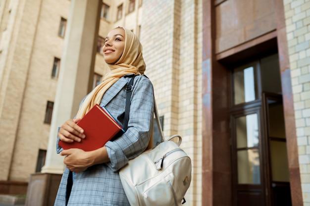 本を持ったアラブの女の子が大学の入り口でポーズをとる。ヒジャーブのイスラム教徒の女性は、屋外で教科書を保持しています。