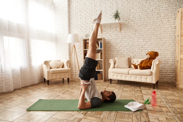 Arab guy does candlestick exercise on gym carpet