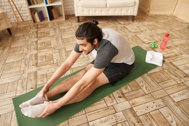 Arab guy does stretching exercise on gym carpet.